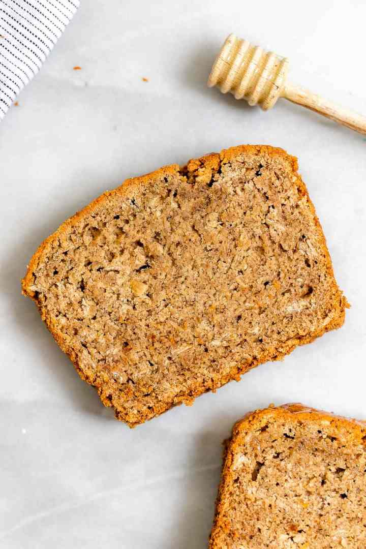Two slices of the gluten free vegan banana bread with a honey comb on the side.