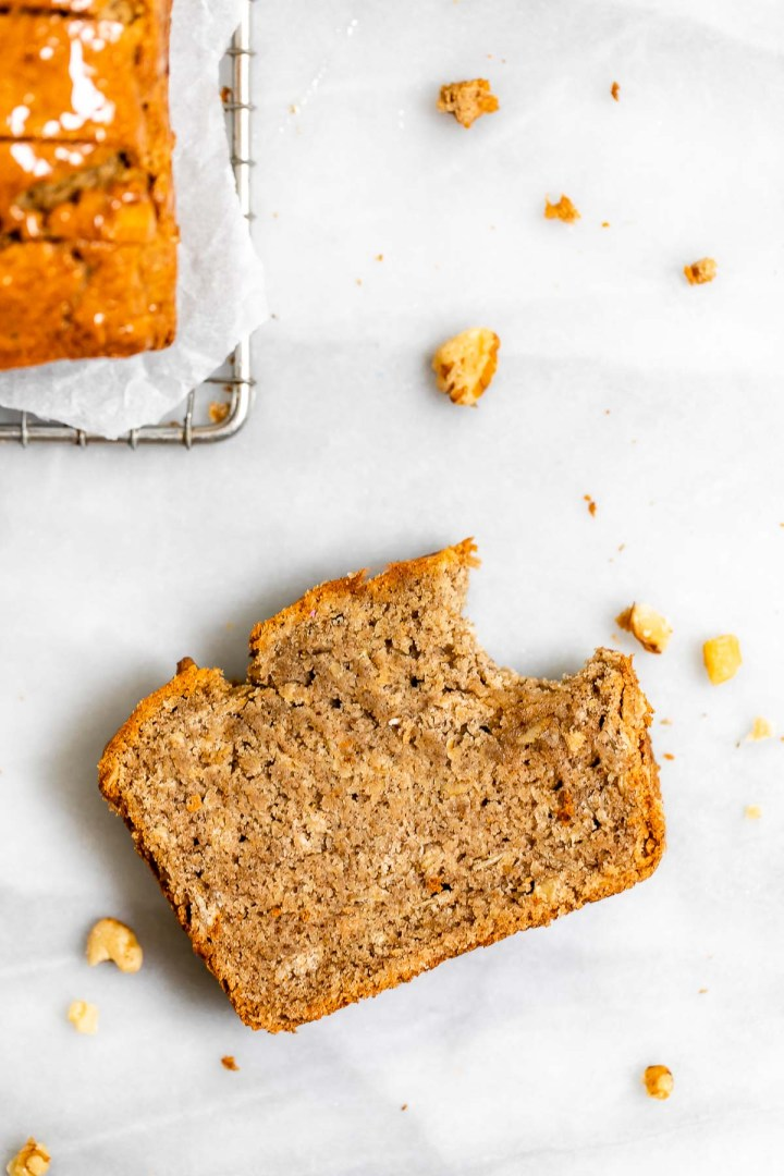 One piece of vegan banana bread with a bite taken out of the corner.