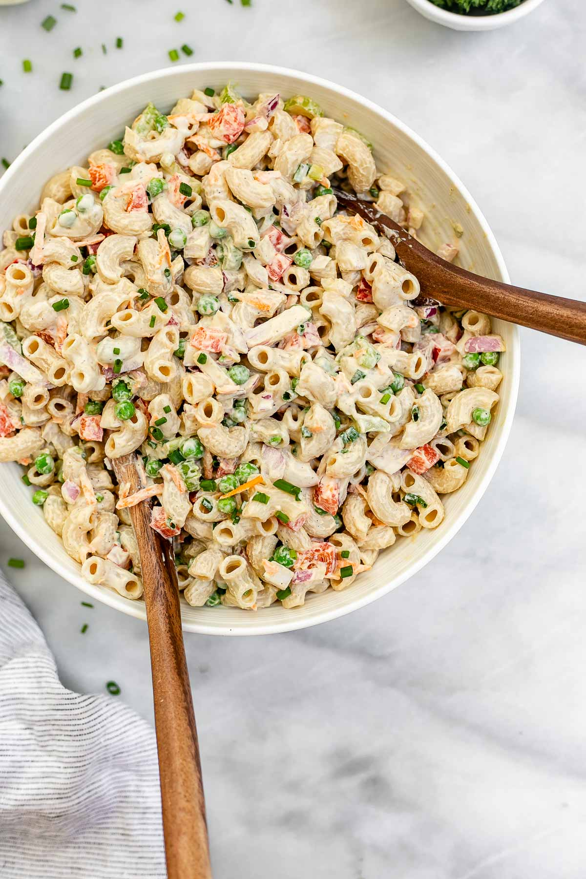 Vegan macaroni salad with two wooden spoons on the side.