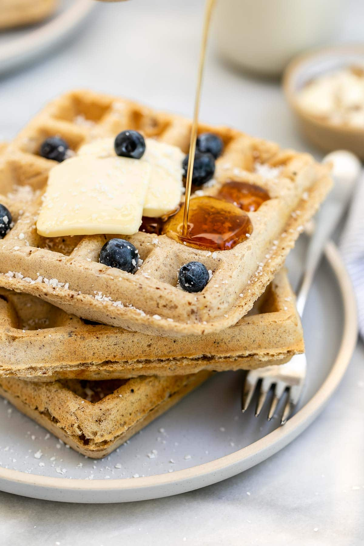Waffles with maple syrup pouring down.