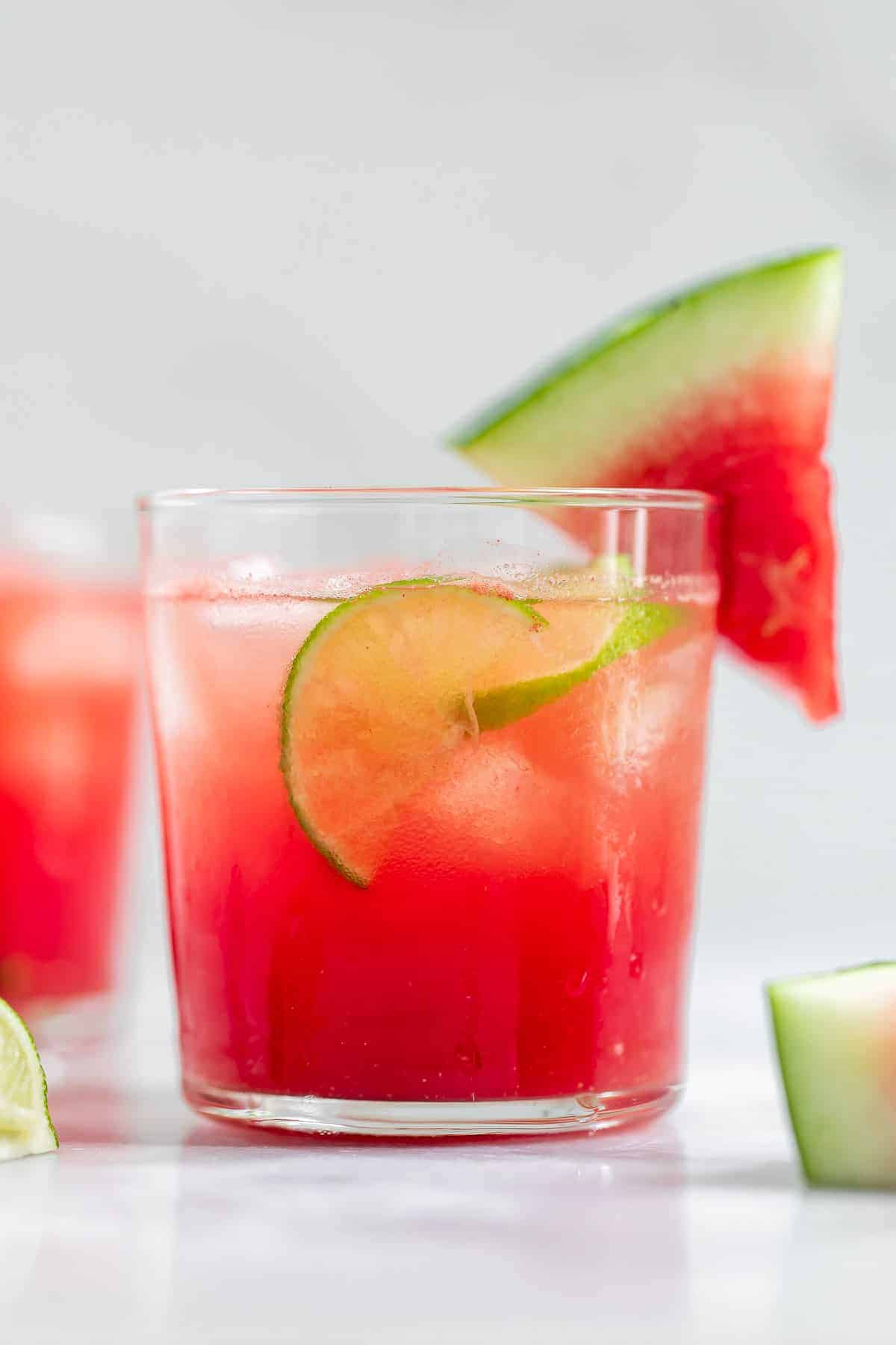 Up close image of the vodka cocktail with lime and watermelon wedges.