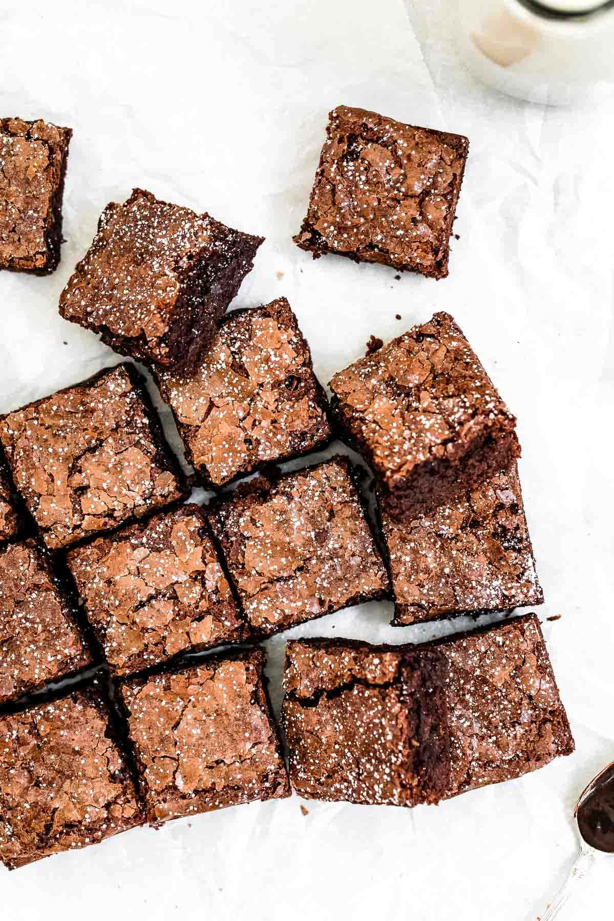 gluten free brownies with powdered sugar on top on parchment paper
