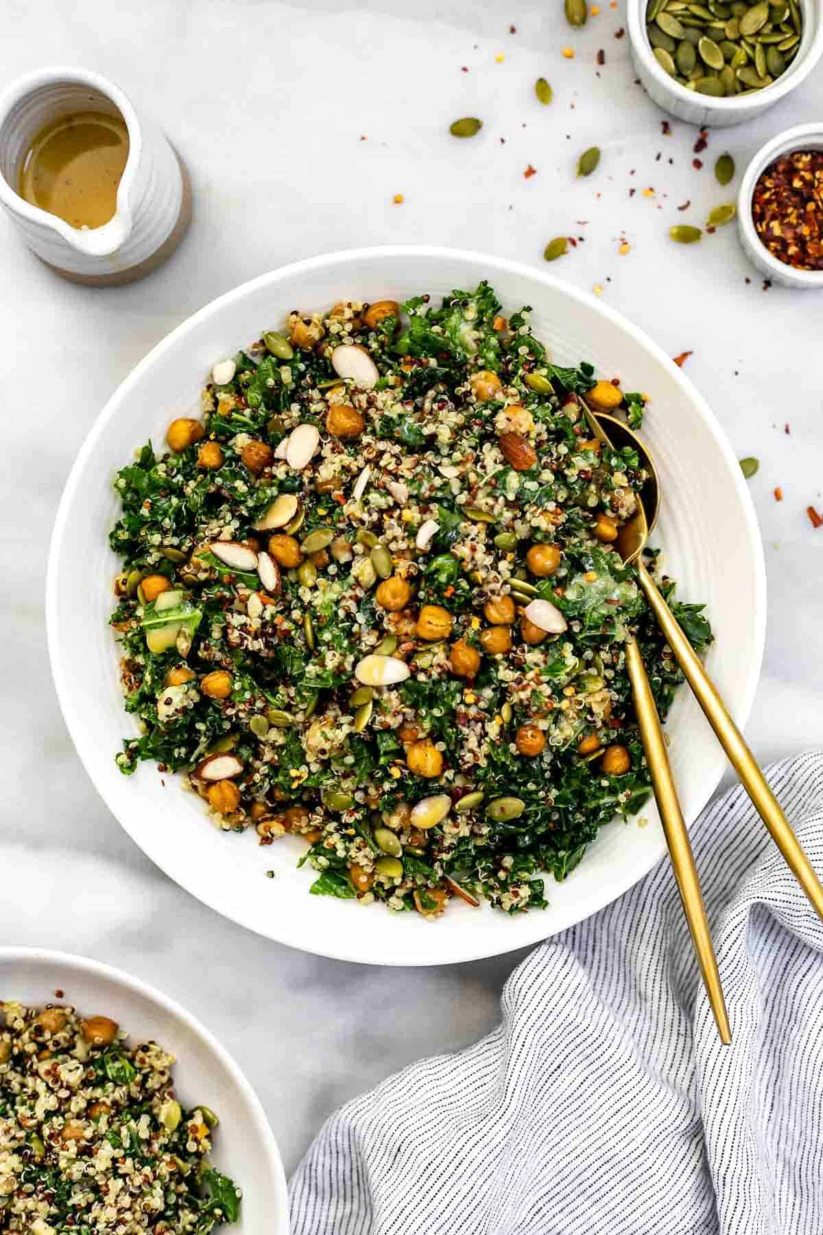 Kale quinoa salad in a white bowl with a stripped towel.