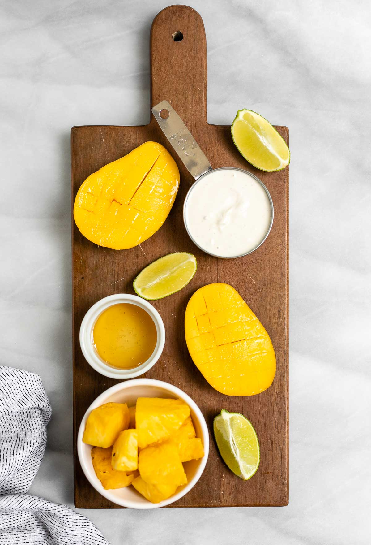 Ingredients for the mango popsicles on a wood board.