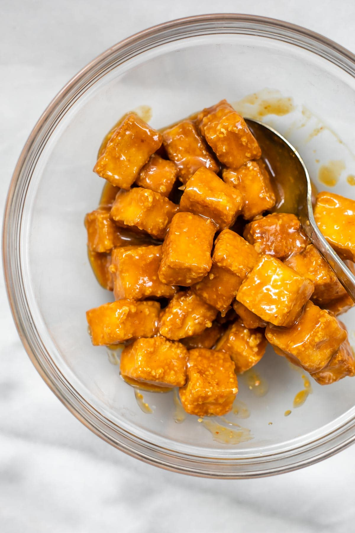 Final orange tofu in a bowl with the sauce on top.