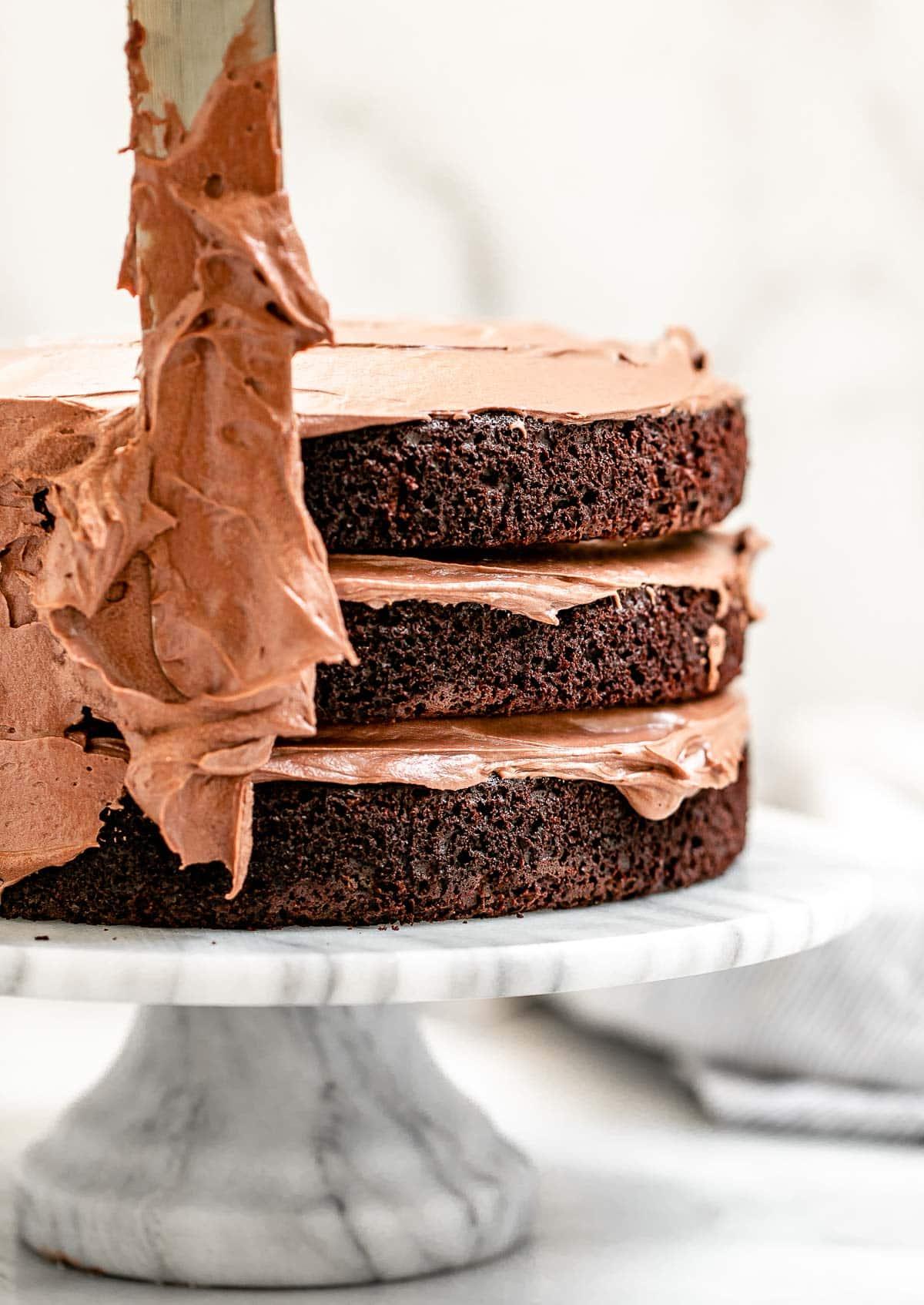 Slathering the buttercream over the cake.
