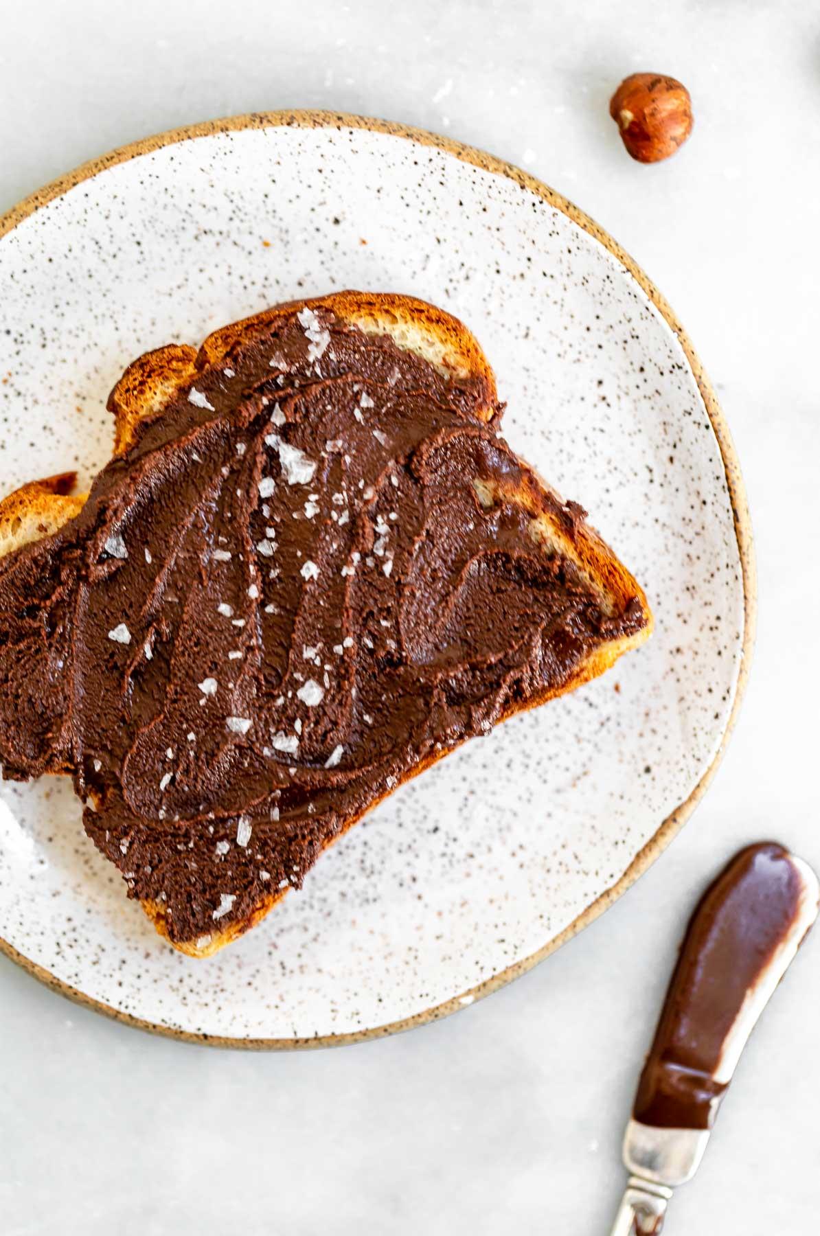 Vegan chocolate nutella on a piece of toast.