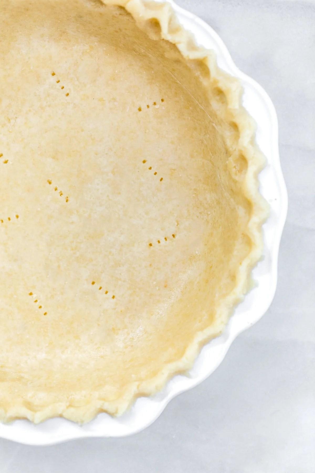 Gluten free pie crust in a white pie plate.