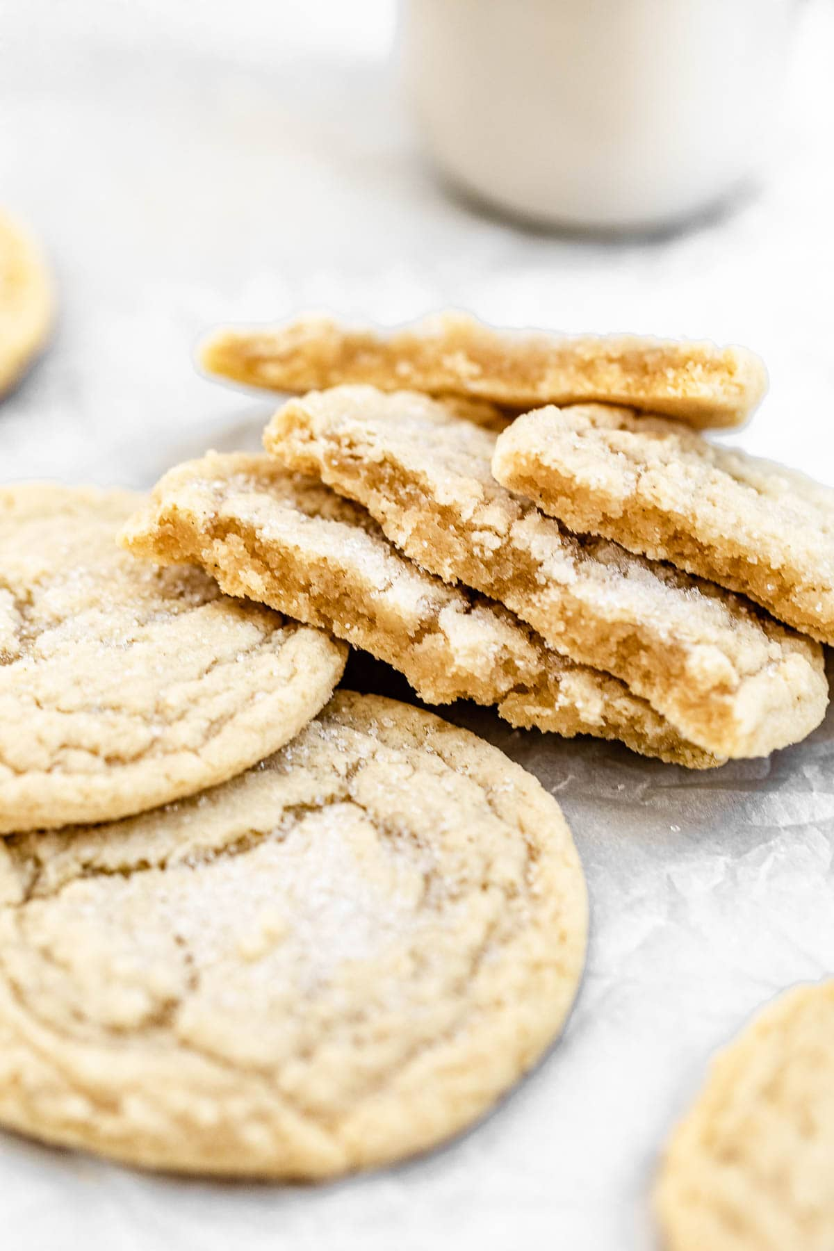 Gluten free sugar cookies cut in half on a piece of parchment paper.