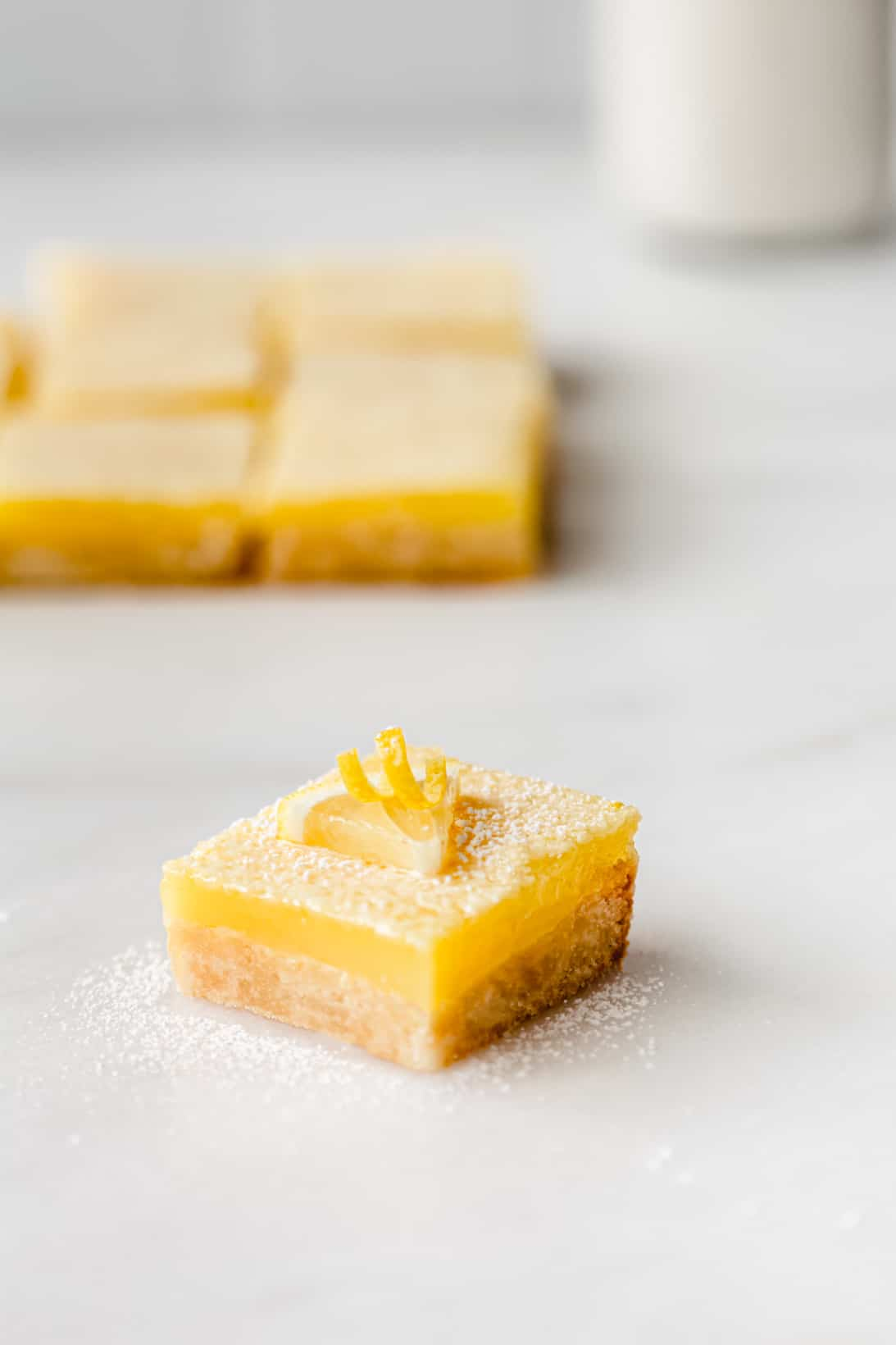 Lemon bars with milk in the background.