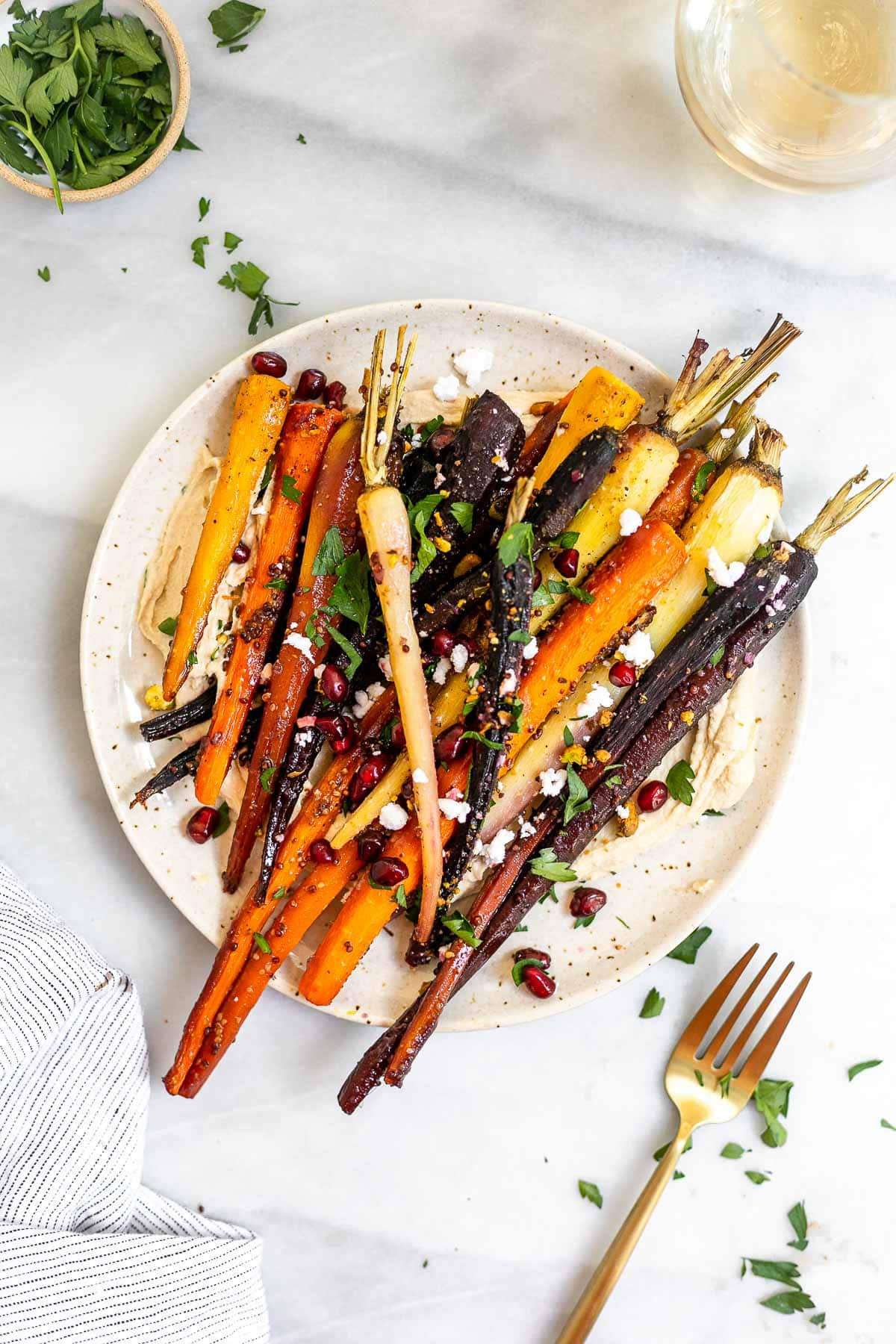 Roasted veggies on a plate with pomegranate on top.