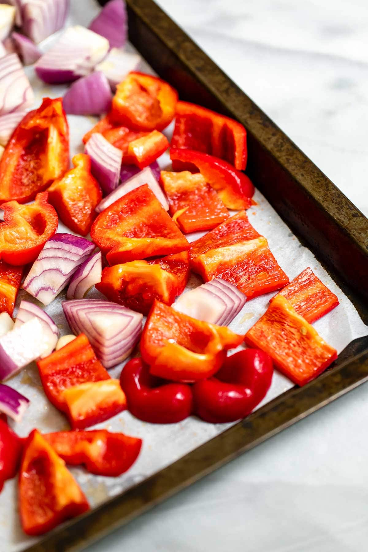Veggies and onions on a baking tray with parchment paper.