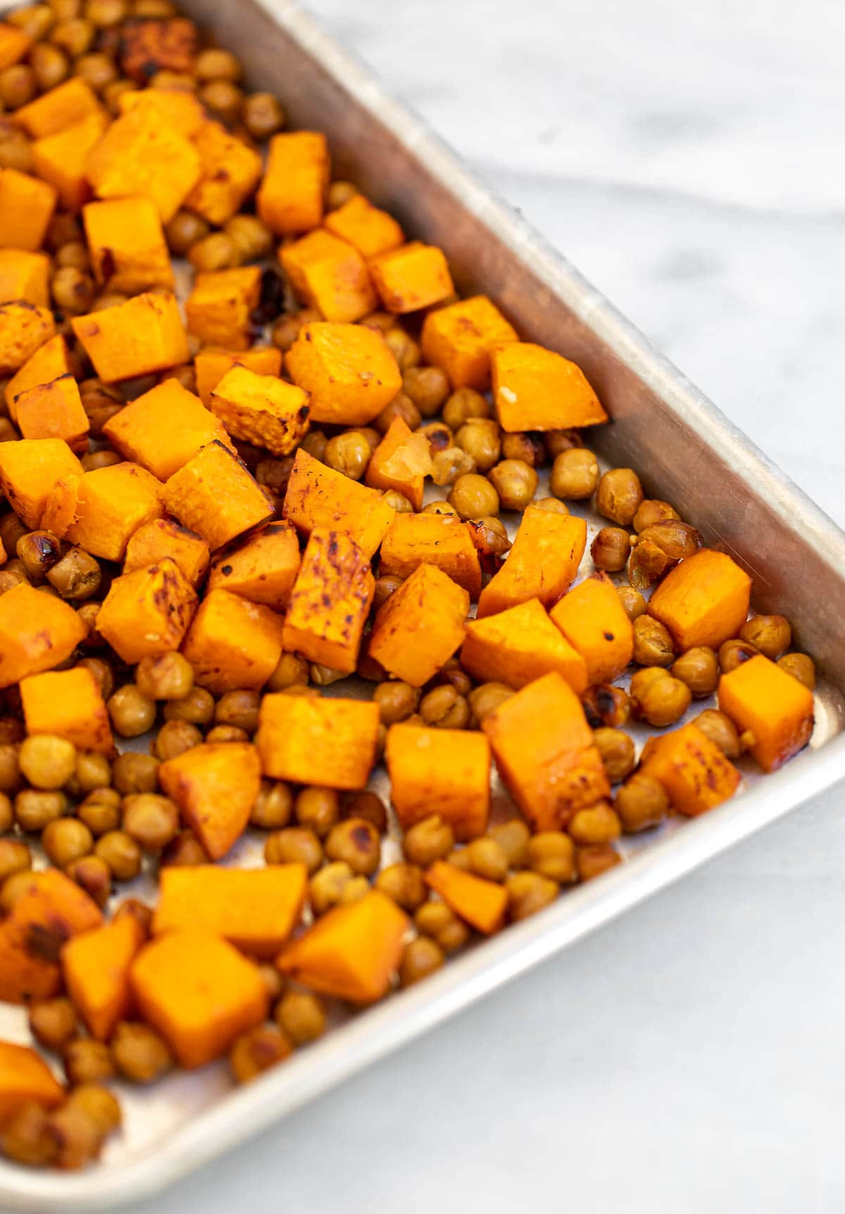 Roasted sweet potatoes and chickpeas on a baking tray.