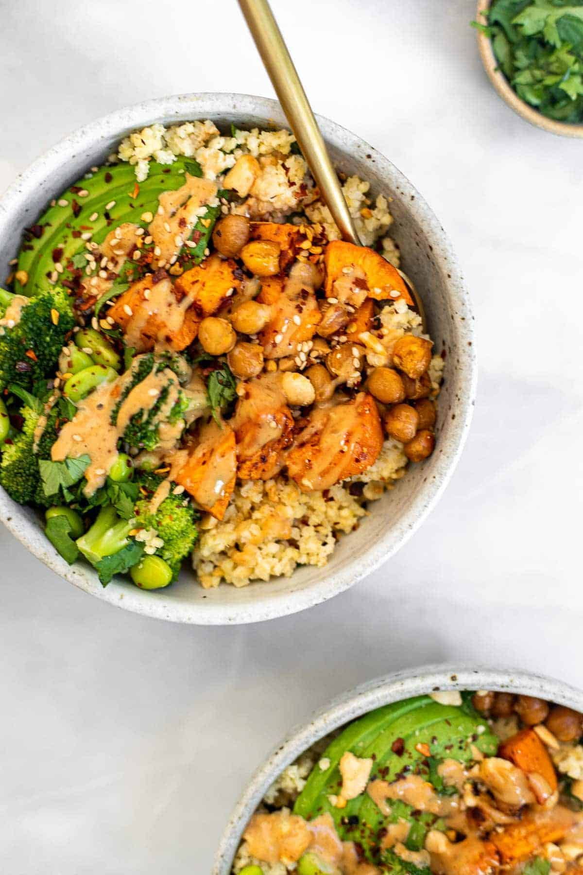 Two buddha bowls with forks on the side with millet and broccoli.