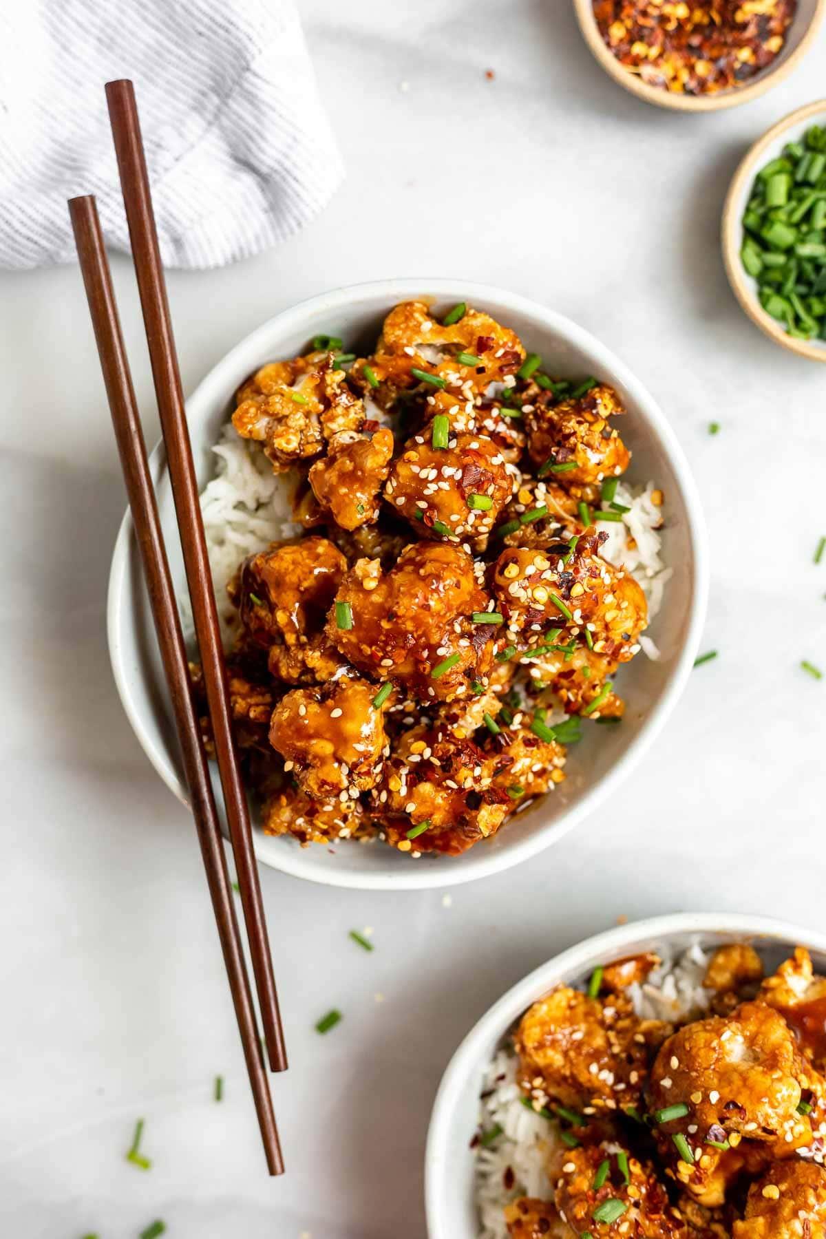 Vegan crispy sesame cauliflower in a bowl with rice and chopsticks.