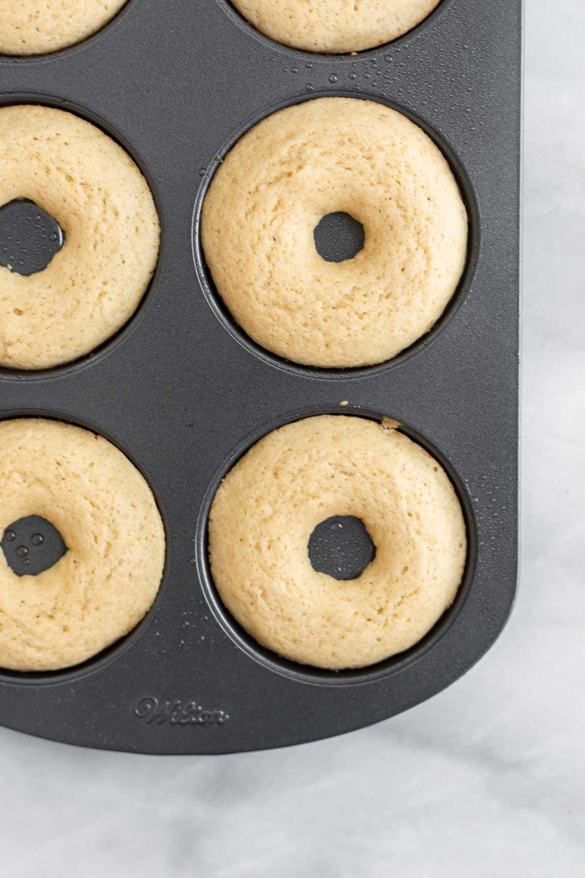 Donuts in the pan after coming out of the oven.