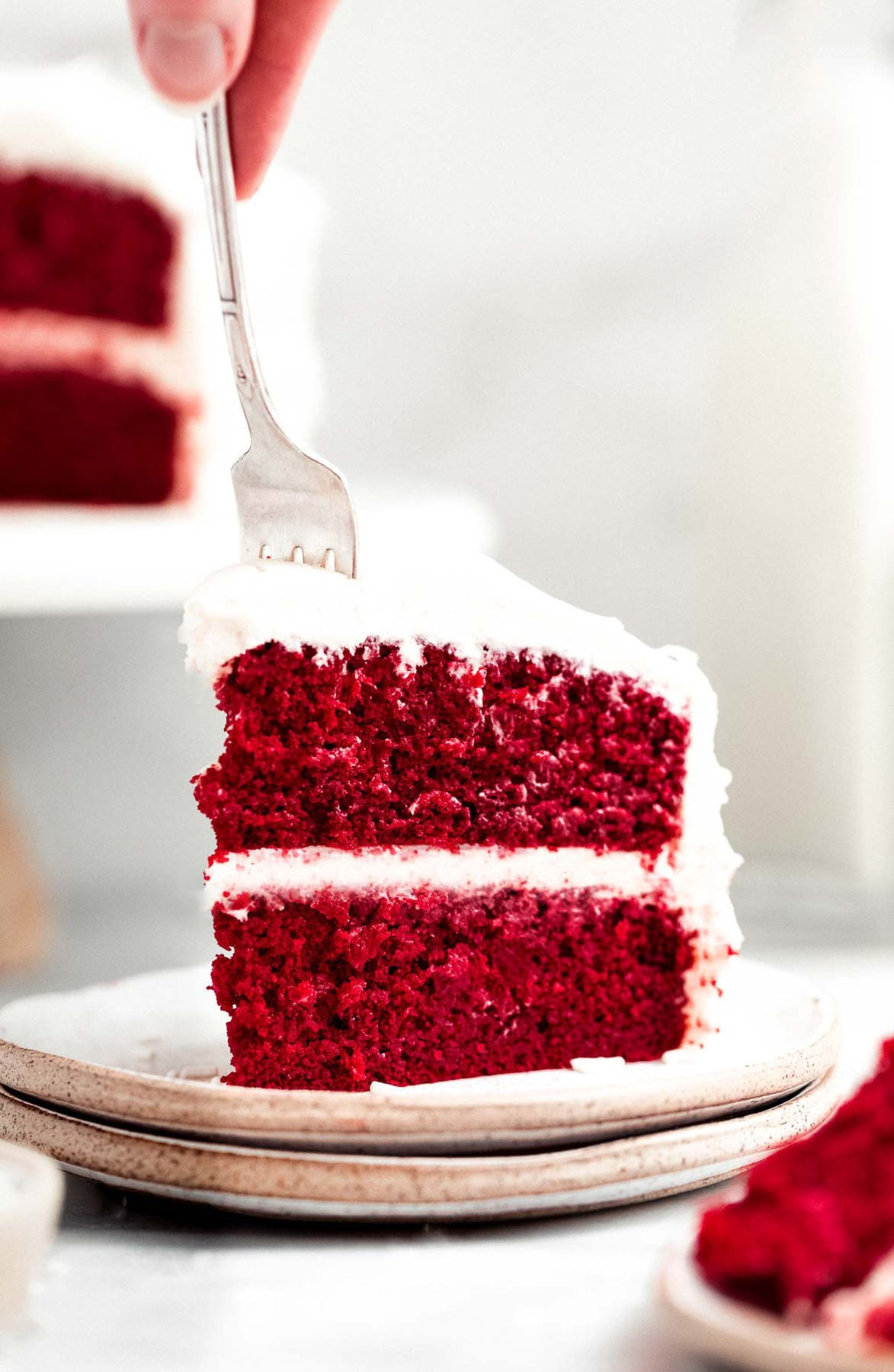 Gluten free red velvet layer cake with a fork taking a bite.