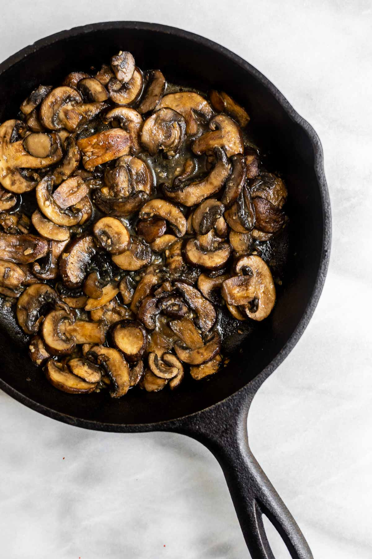 Mushrooms sauteed in a black pot with garlic.
