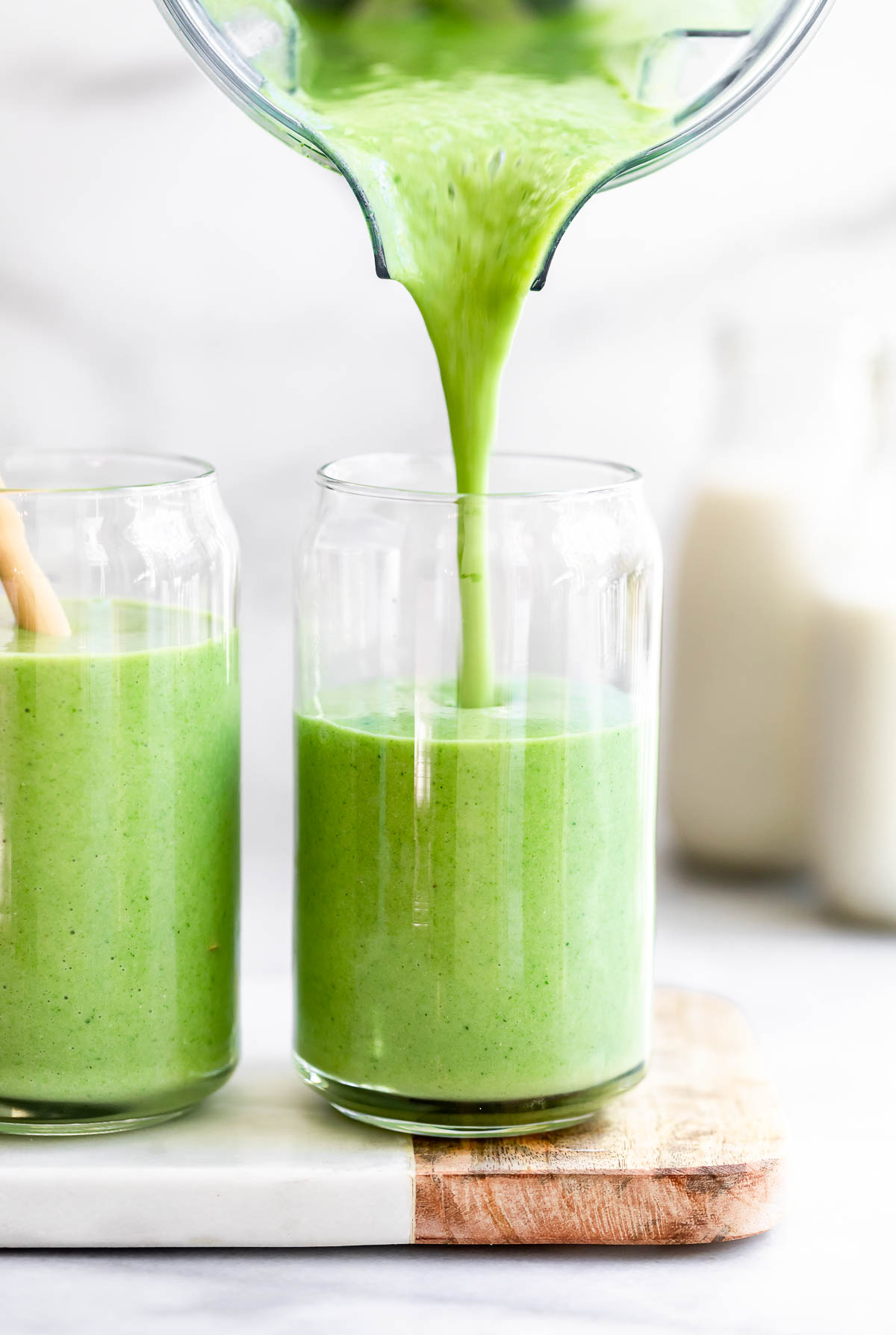 pouring the green smoothie into two glasses