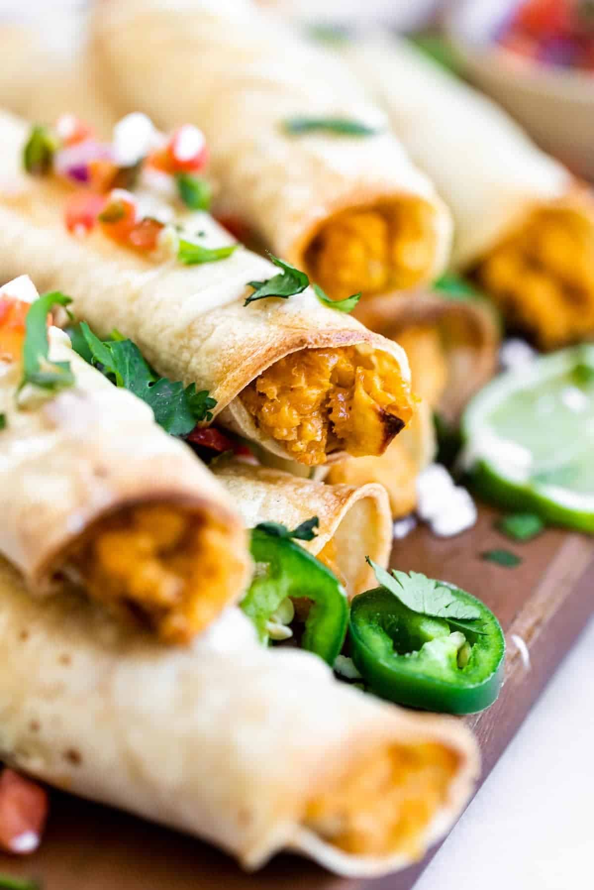 vegan chickpea taquitos on a wood board with jalapeno