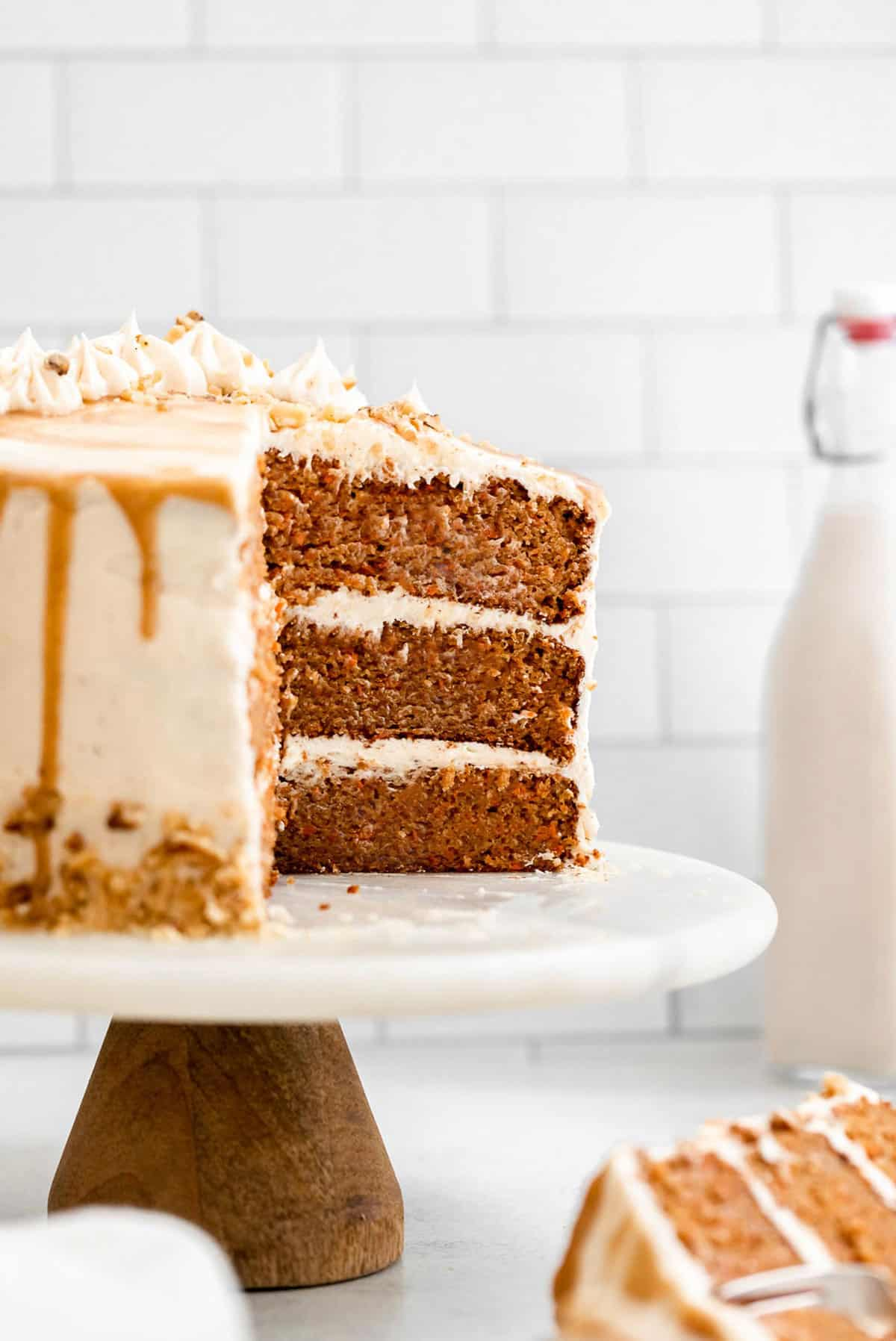 three layer gluten free carrot cake on a cake stand with milk in the back