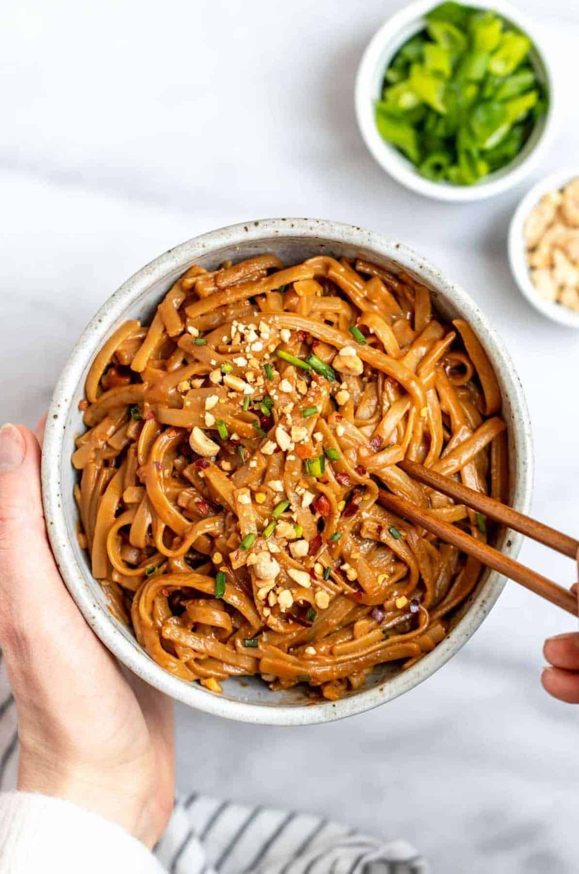 hands holding up a bowl with peanut butter noodles