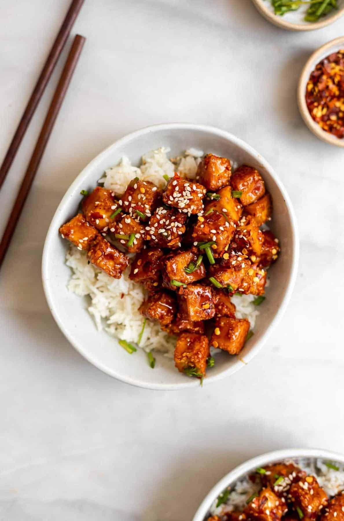 vegan teriyaki tofu in two bowls on top of rice with chopsticks.