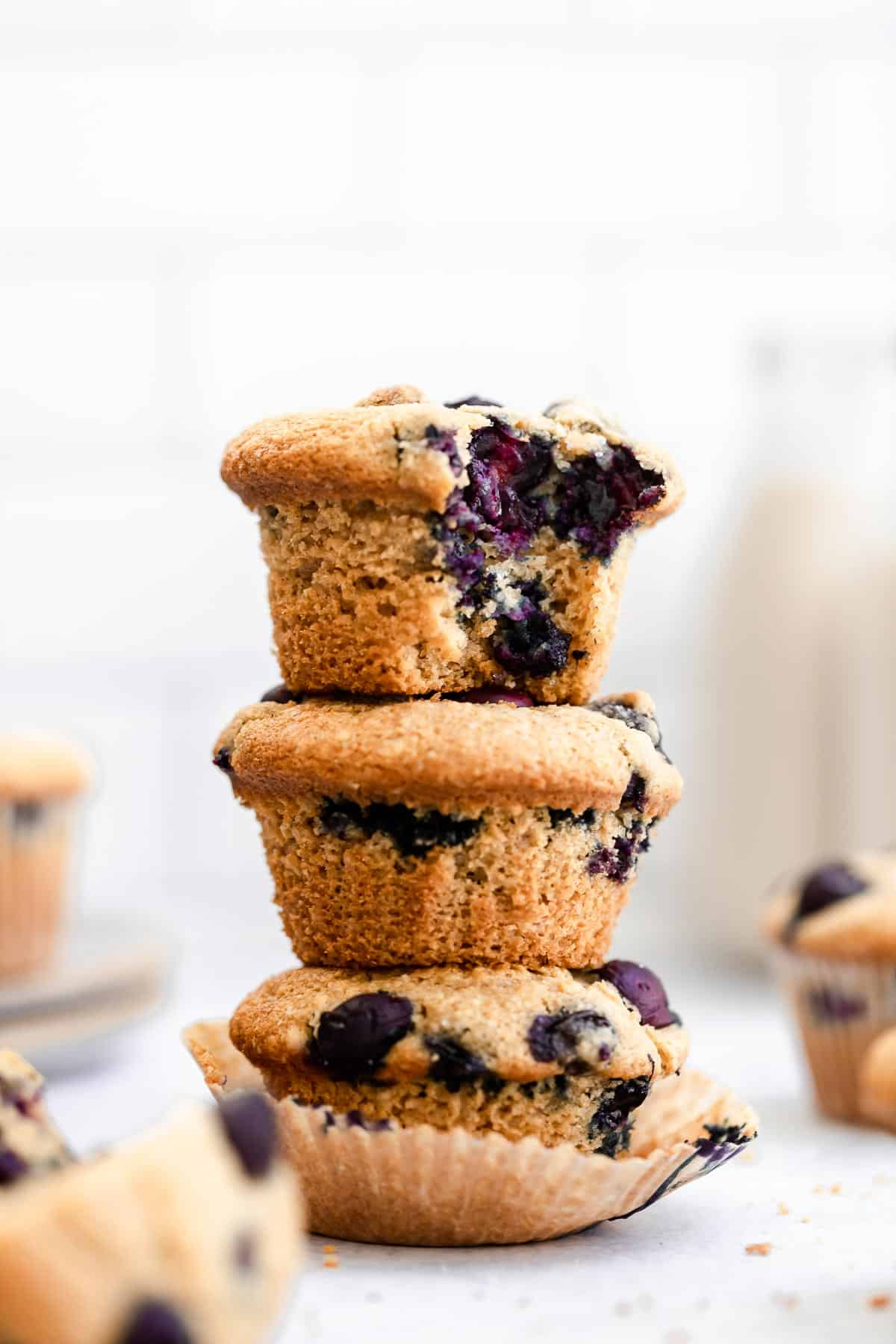 three blueberry muffins with a bite taken out