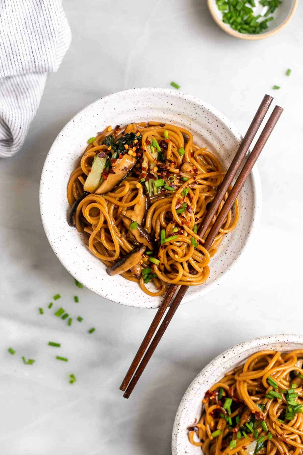 two bowls of stir fry noodles with chopsticks and mushrooms