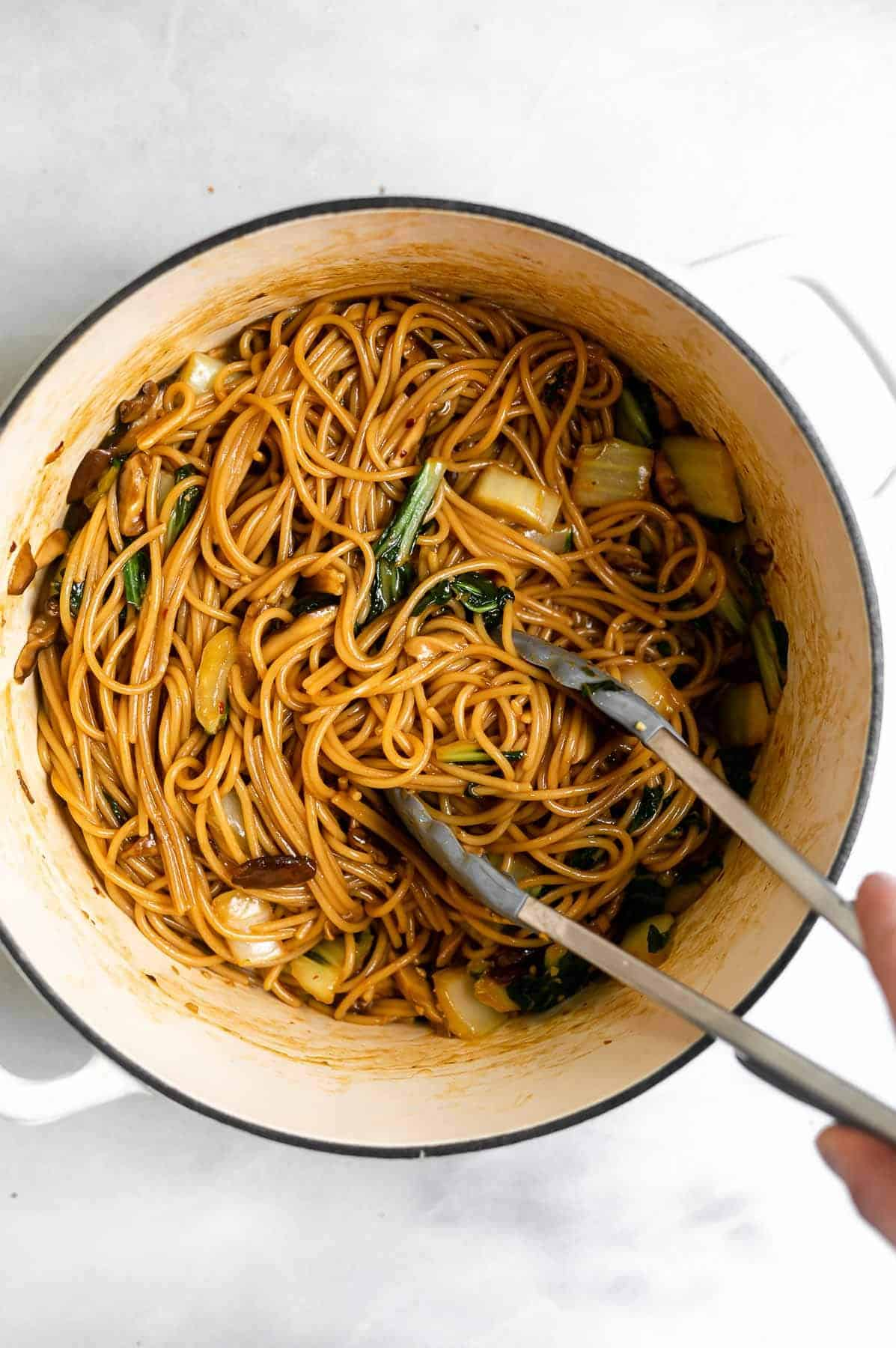 vegan teriyaki noodles in a large white pot with tongs