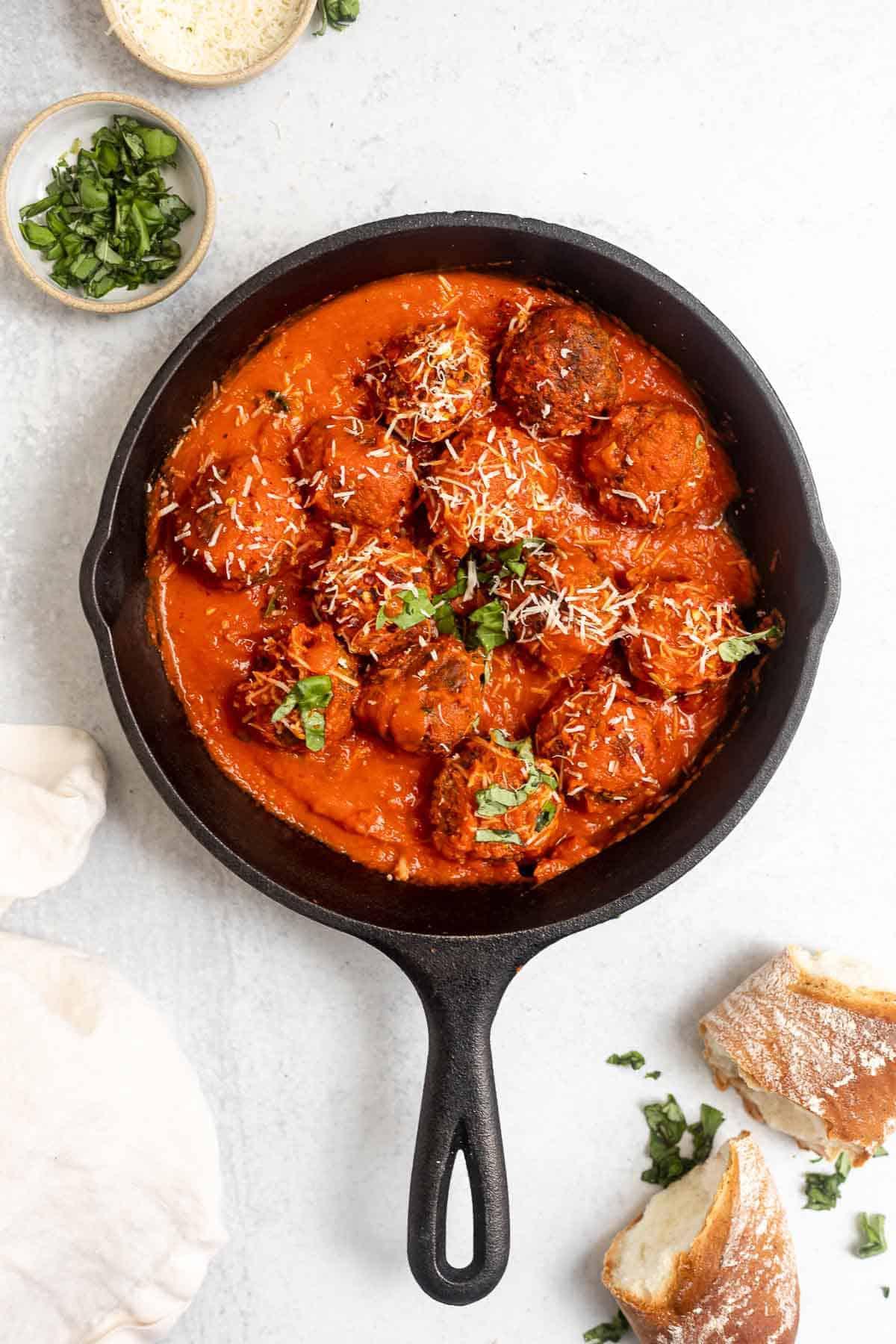 vegan lentil meatballs in a black skillet with fresh basil