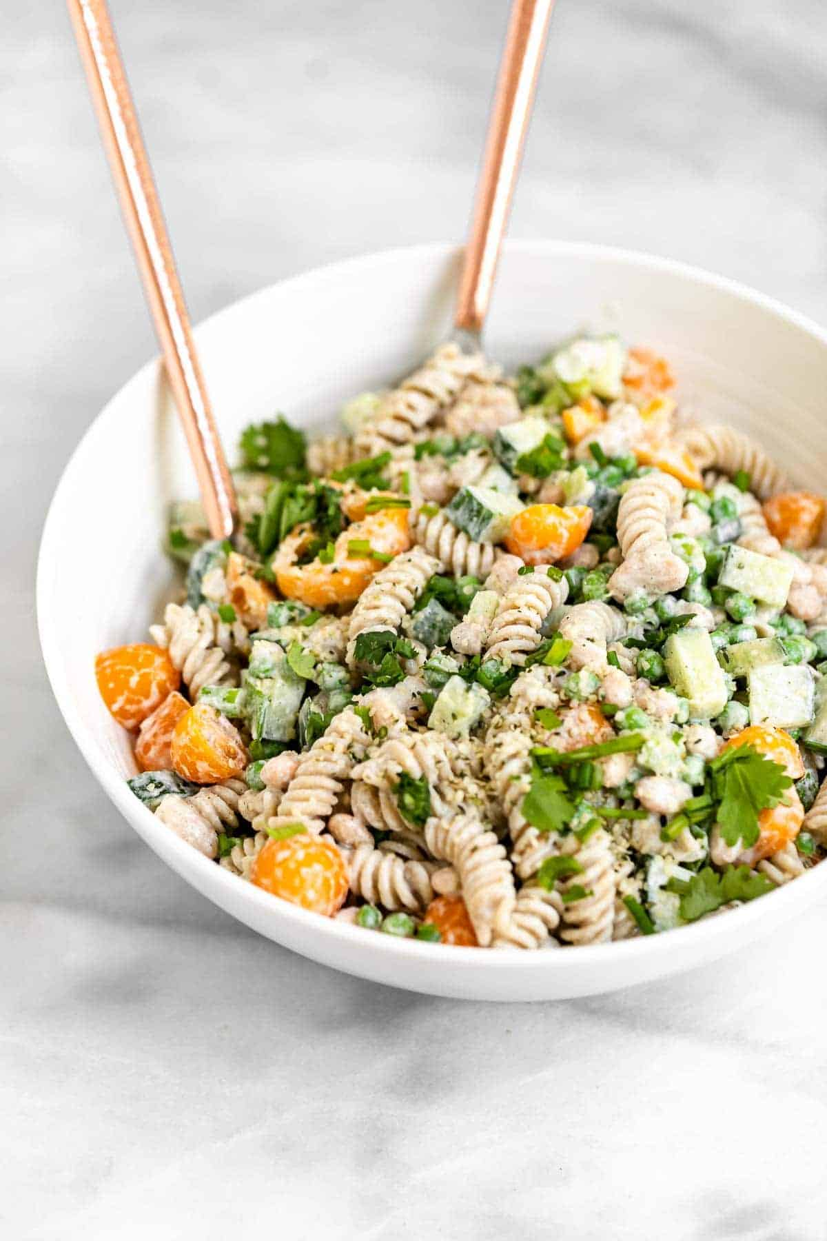 pasta salad in a white bowl with spoons on the side