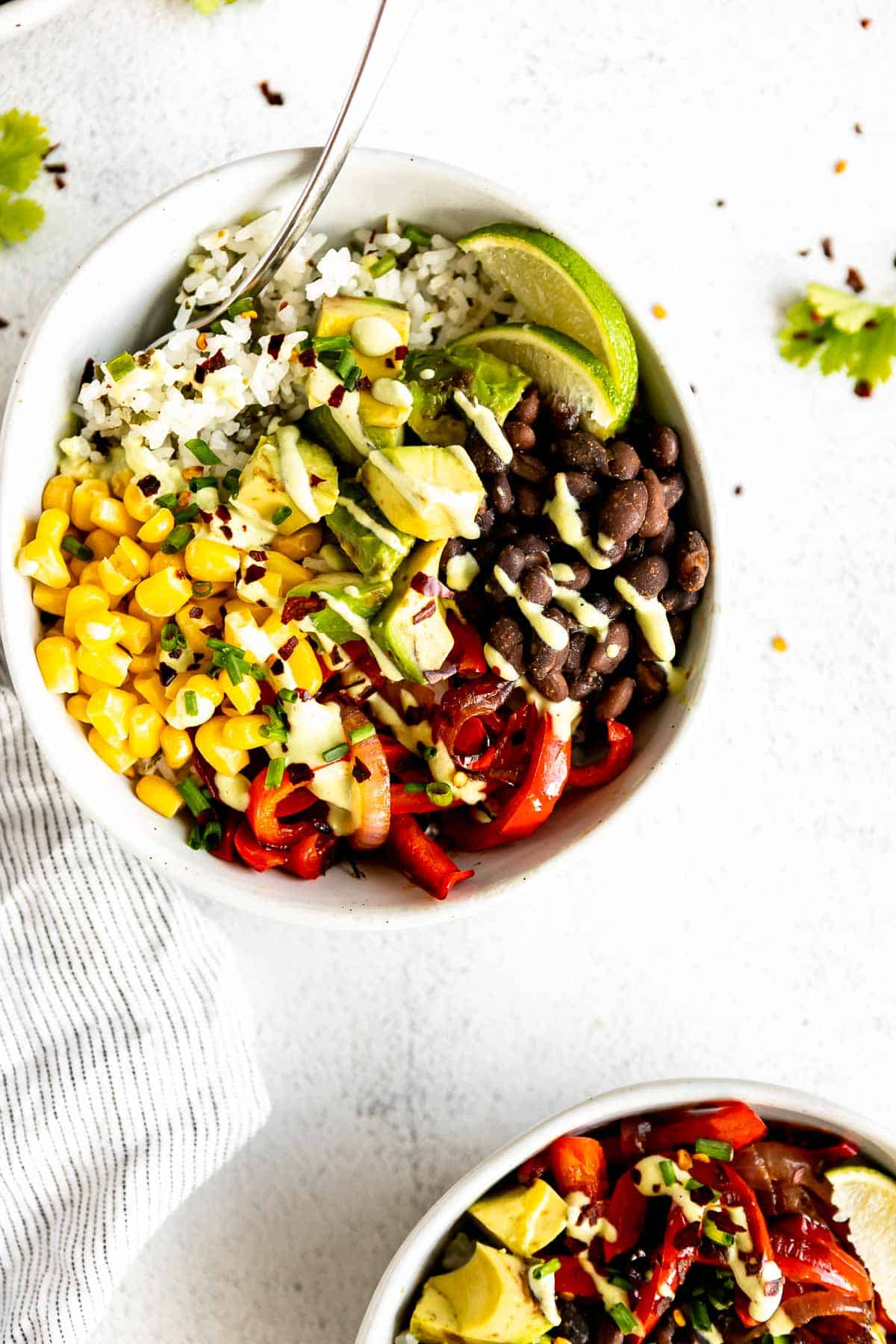 two vegan burrito bowls with sauteed peppers and cilantro lime crema
