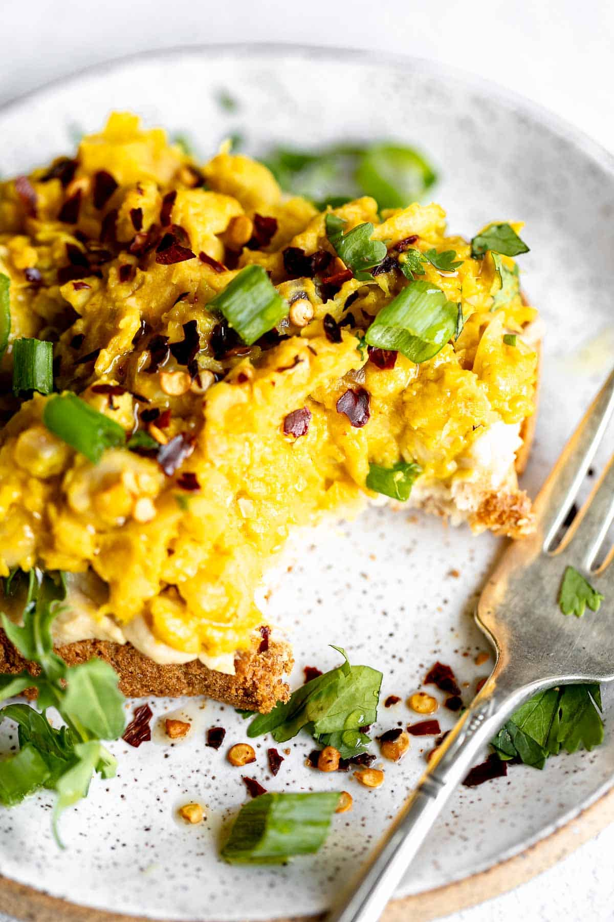 vegan chickpea scramble on a piece of toast with a bite taken out