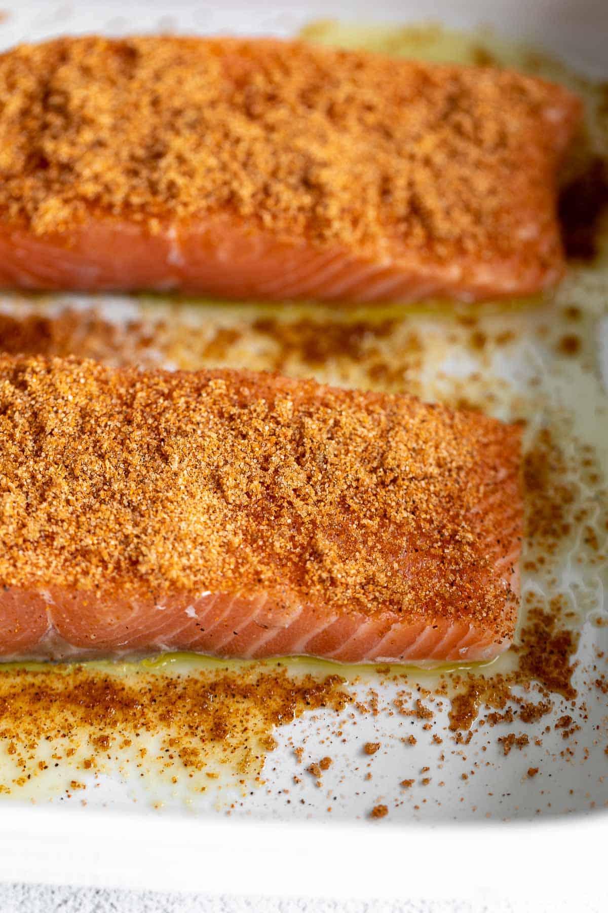 salmon in a baking pan with seasonings before baking