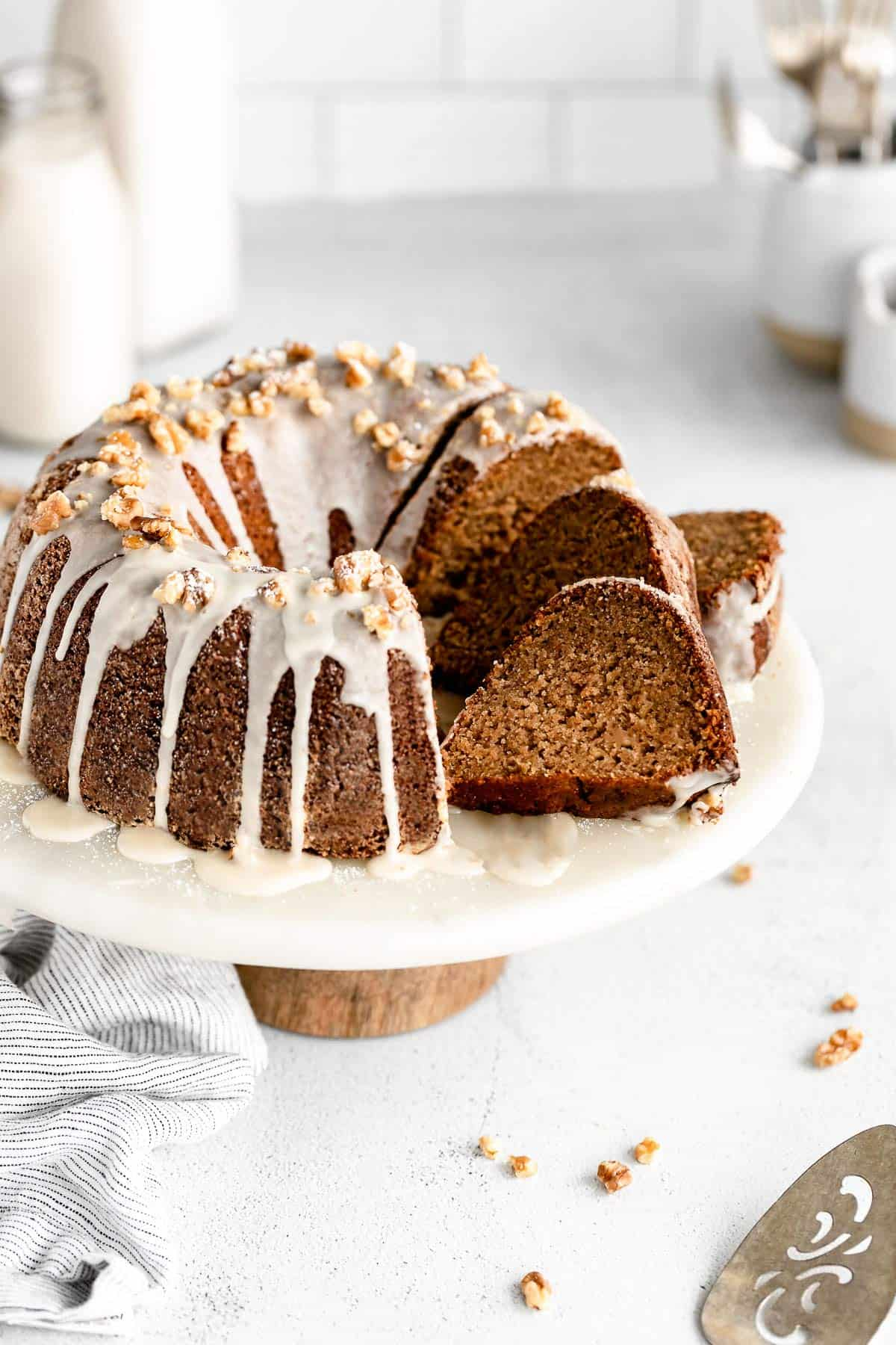 gluten free apple bundt cake on a stand with three slices on the side