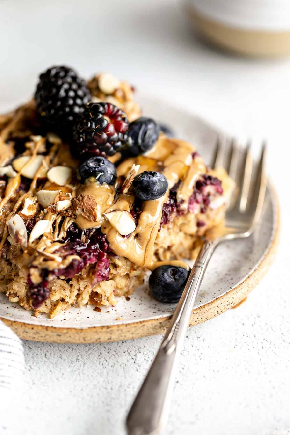 vegan baked oatmeal on a plate with a fork and peanut butter