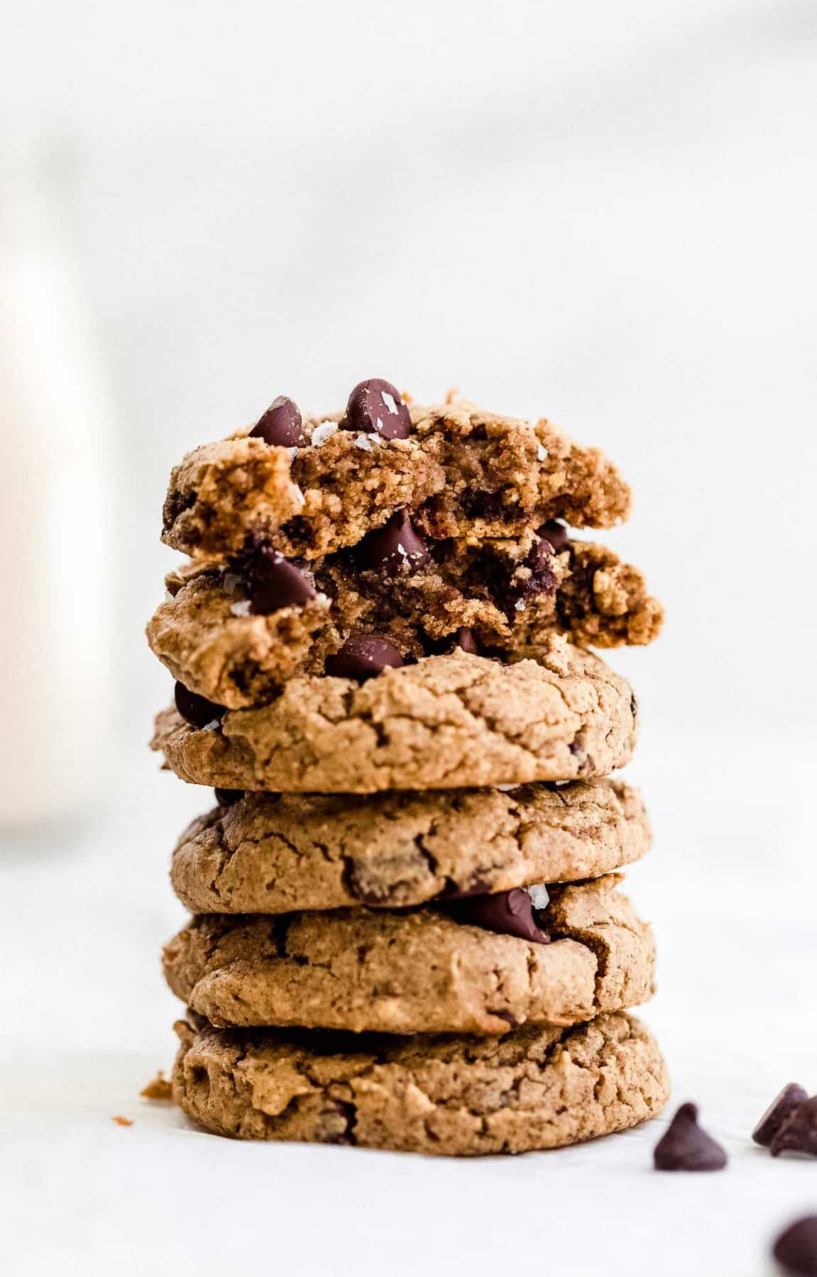 Five cookies stacked on each other with a jar of milk in the back.