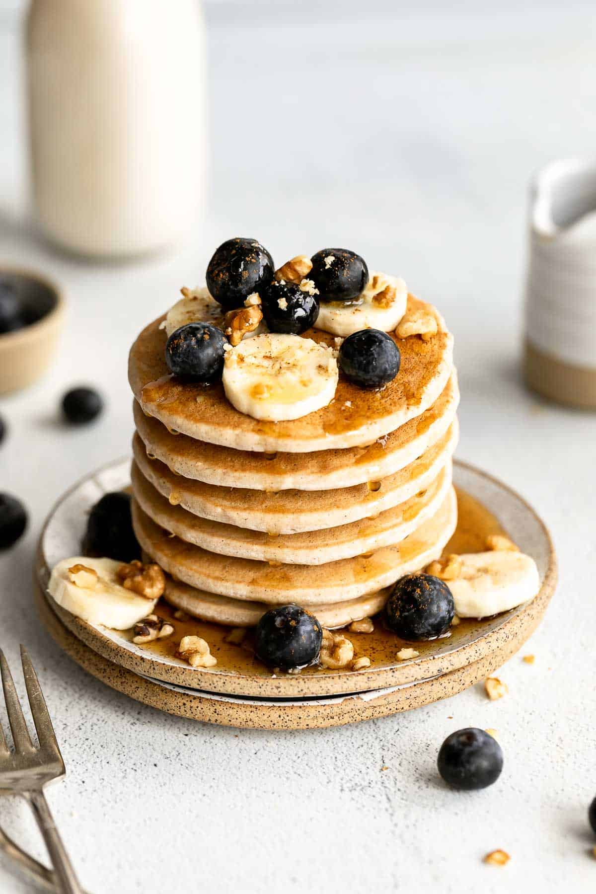 vegan buckwheat pancakes on a plate with berries and banana