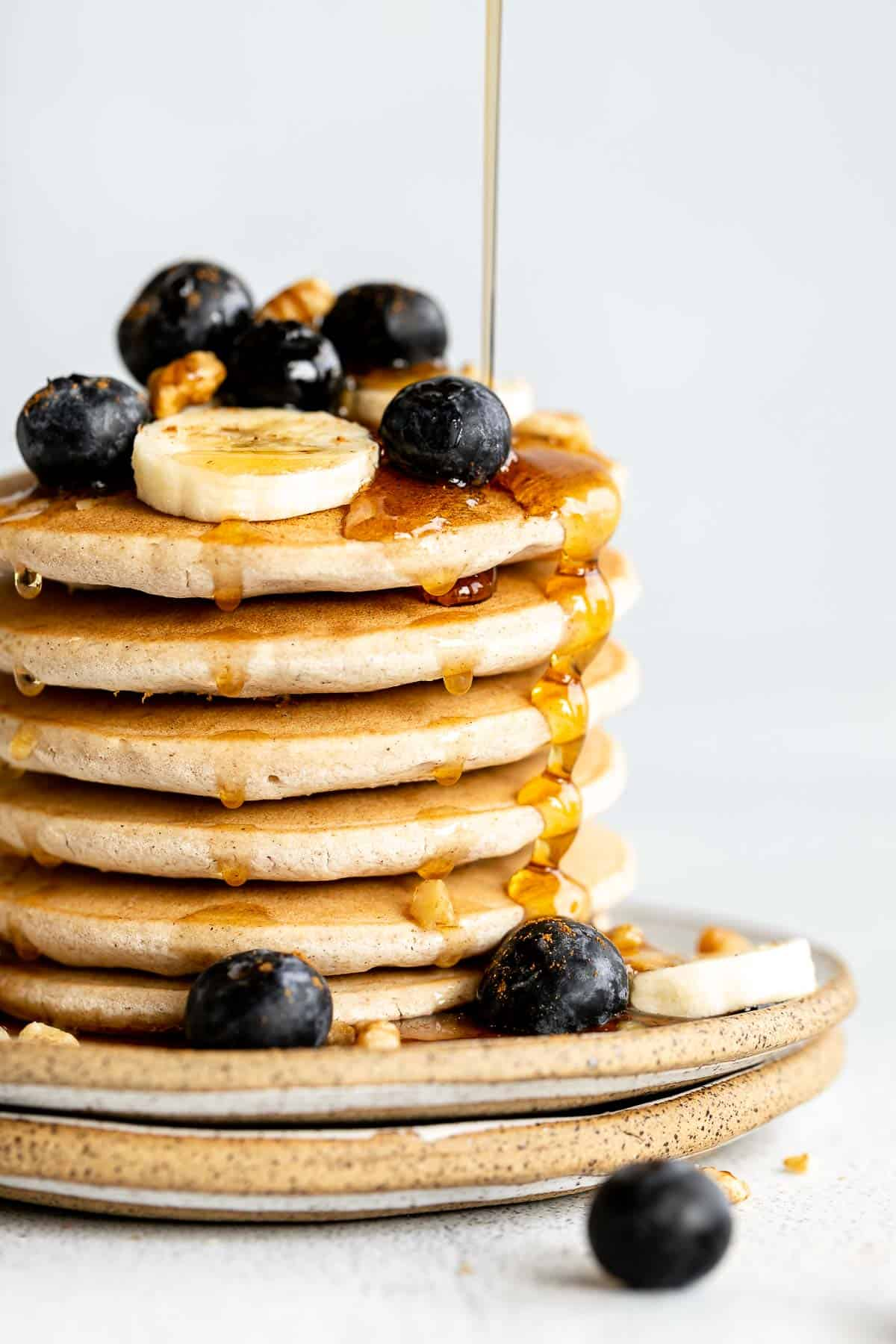 up close of the stack of pancakes with maple syrup drips