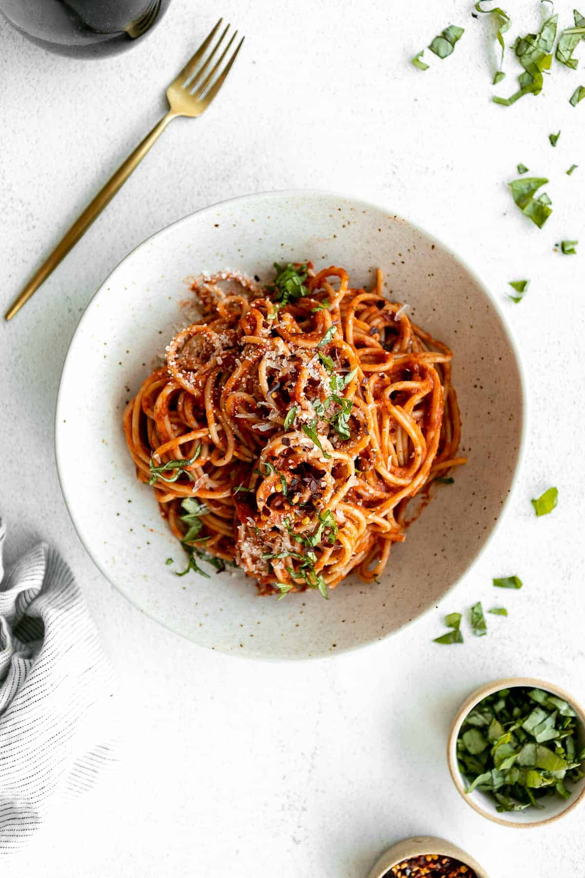 final spaghetti in a bowl with parmesan and basil