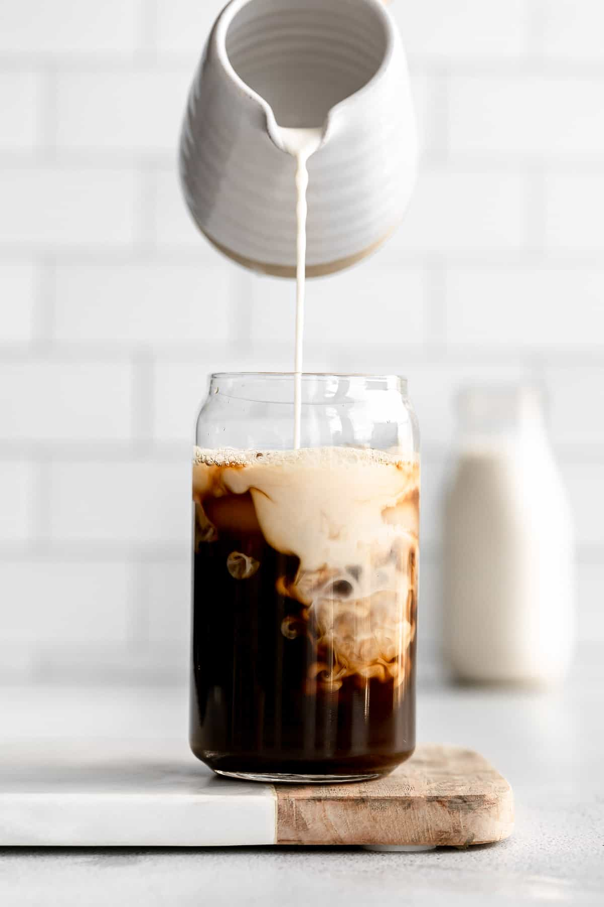 pouring the homemade walnut milk in a cup of iced coffee