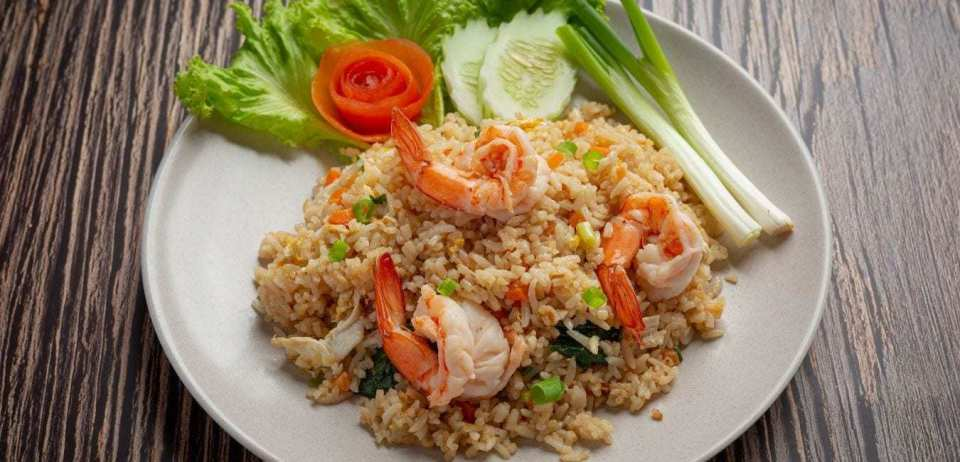 Shrimp fried rice on a white plate with vegetables.