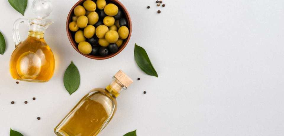 Fresh olives and olive oil with black pepper spices on a white table.