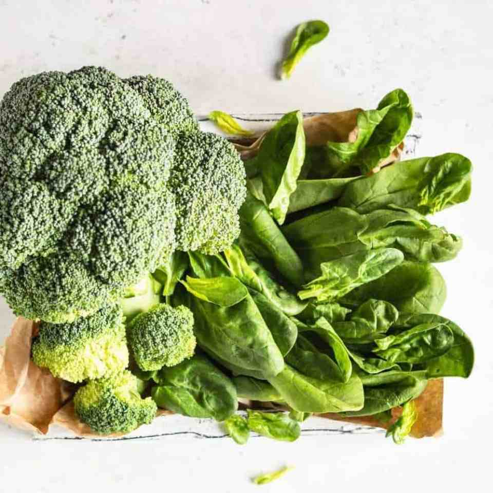 Spinach and broccoli, blood sugar balancing foods, on na white countertop.