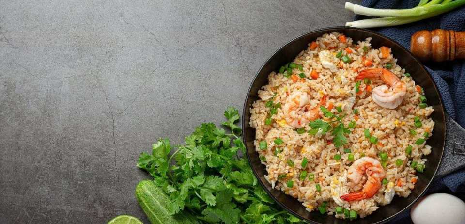 Shrimp fried rice with scallions, parsley, and cucumber on a grey countertop.