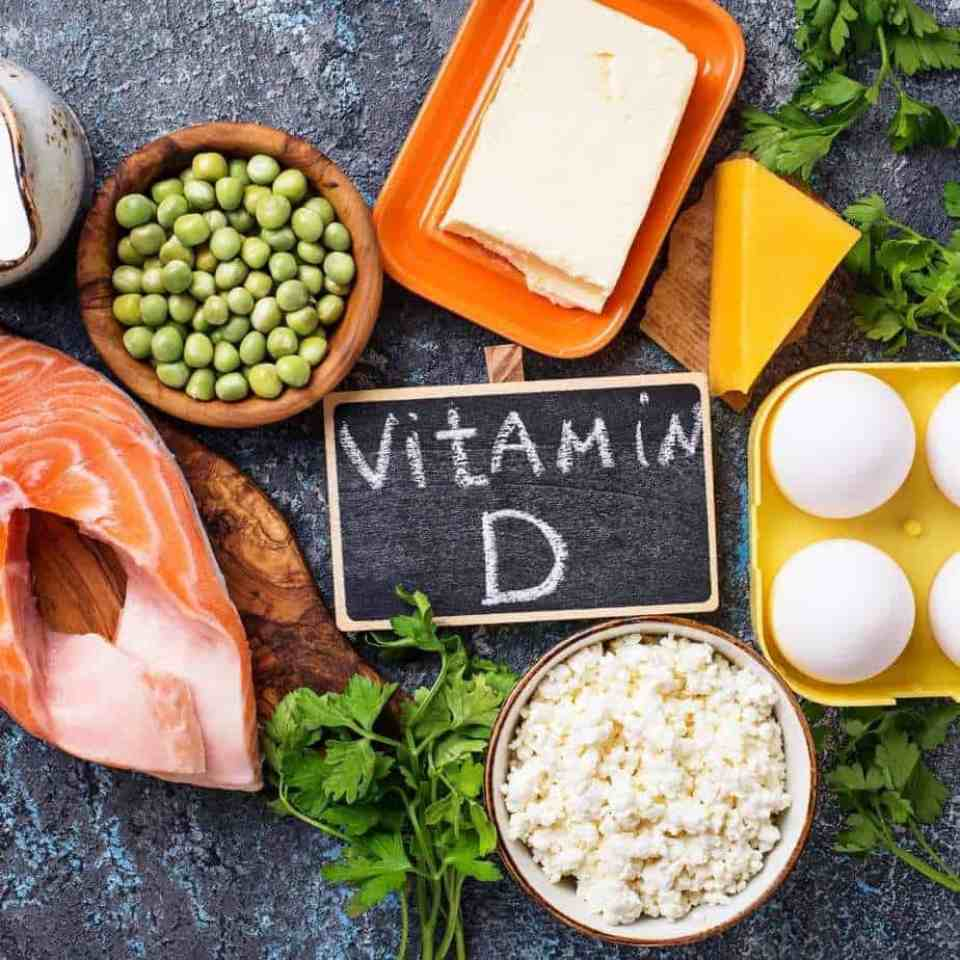 Foods like eggs, dairy, cheese, salmon on a blue countertop. Important vitamin D foods.