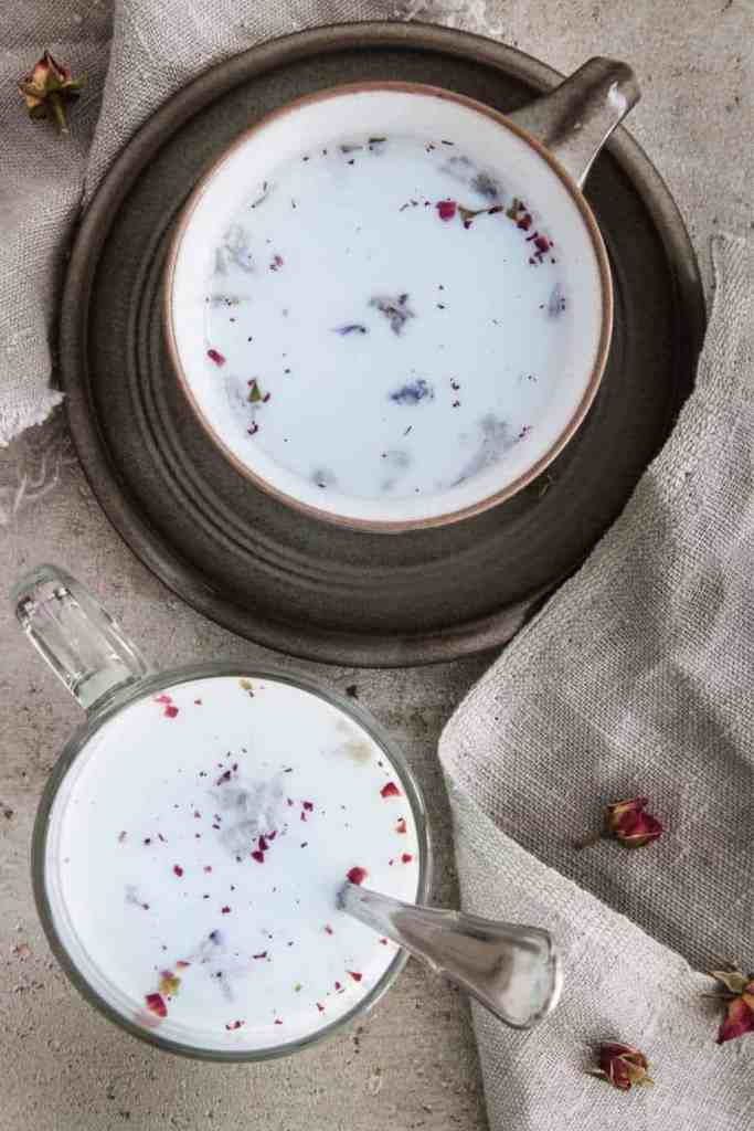 A blueberry moon milk drink in a mug on a table with dried rose petals.