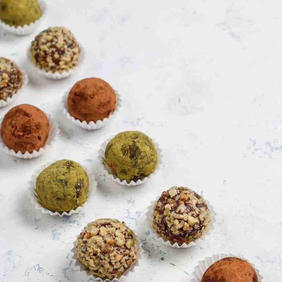 Homemade healthy snack of vegan raw energy protein balls with dates and nuts. on a white table.