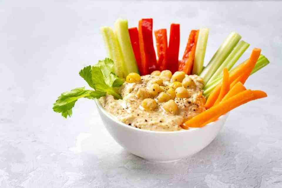 Delicious and healthy snack bowl with fresh hummus dip and cut vegetable sticks.